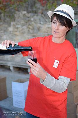 Une vigneronne du Pic Saint Loup faisant découvrir son vin rouge au au festival de musique et vins du Festapic